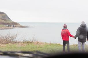 Couple holding hands on cliff overlooking oceanの写真素材 [FYI02187041]