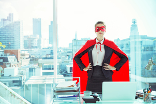 Businesswoman wearing cape and mask in officeの写真素材 [FYI02187052]