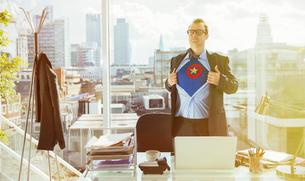 Businessman revealing superhero costume under suitの写真素材 [FYI02187054]