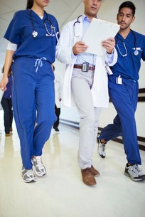 Doctor and nurses reading medical chart in hospital hallwayの写真素材 [FYI02187062]