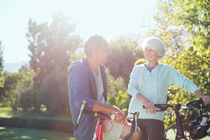 Senior couple with bicycles in parkの写真素材 [FYI02187066]