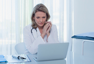 Female doctor sitting at desk with laptop in officeの写真素材 [FYI02187082]