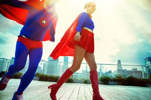 Superheroes running on city rooftopの写真素材 [FYI02187098]