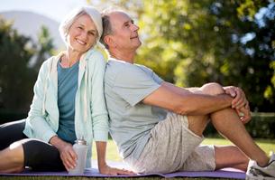Senior couple sitting on yoga mat in parkの写真素材 [FYI02187126]