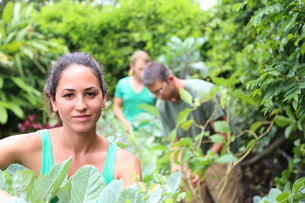 Portrait of young woman in garden, man and woman in backgroundの写真素材 [FYI02187161]