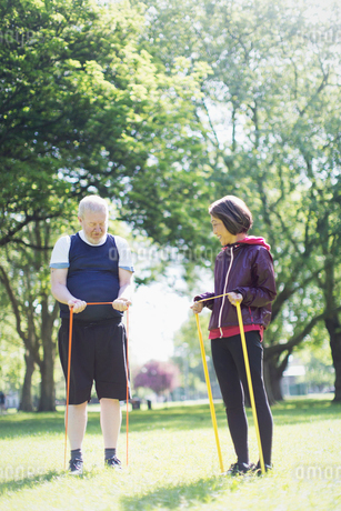 Active senior couple exercising, stretching with resistance bands in sunny parkの写真素材 [FYI02187162]