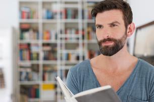 Man reading book in living roomの写真素材 [FYI02187176]