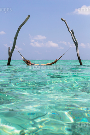 Young woman laying in hammock over tranquil blue ocean, Maldives, Indian Oceanの写真素材 [FYI02187184]