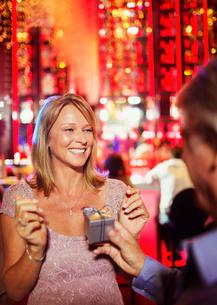 Man handing gift to woman in barの写真素材 [FYI02187186]