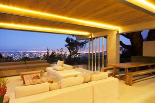 Modern living room overlooking illuminated cityscape at nightの写真素材 [FYI02187191]