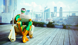Superhero reading newspaper on city rooftopの写真素材 [FYI02187195]