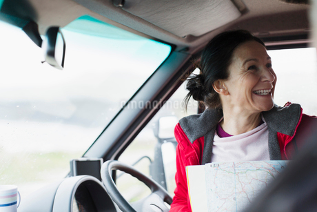 Happy woman with map in motor homeの写真素材 [FYI02187229]