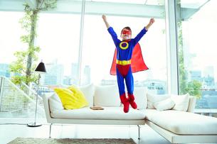 Boy superhero jumping off living room sofaの写真素材 [FYI02187243]