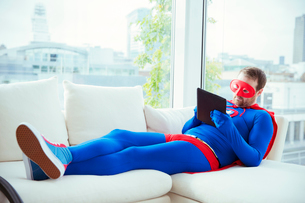 Superhero using digital tablet on living room sofaの写真素材 [FYI02187255]