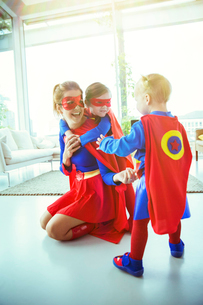Superhero mother and children playing in living roomの写真素材 [FYI02187265]
