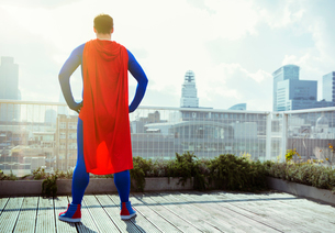 Superhero looking at view from city rooftopの写真素材 [FYI02187270]