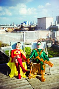 Superhero couple sitting on city rooftopの写真素材 [FYI02187271]