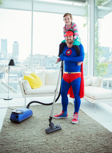 Superhero father vacuuming and carrying daughter on shouldersの写真素材 [FYI02187302]