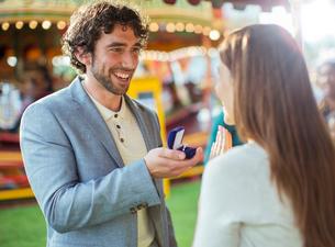 Man proposing to girlfriend in amusement parkの写真素材 [FYI02187309]