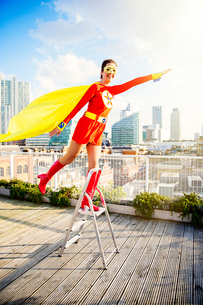 Superhero standing on stepladder on city rooftopの写真素材 [FYI02187319]