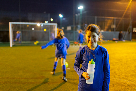 Portrait smiling girl soccer player drinking water on field at nightの写真素材 [FYI02187321]