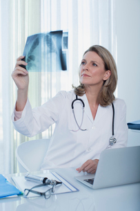 Female doctor looking at x-ray at desk with laptop in officeの写真素材 [FYI02187347]