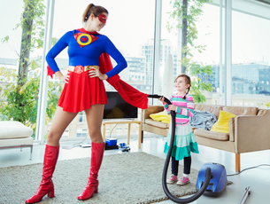 Daughter of superhero vacuuming her cape in living roomの写真素材 [FYI02187355]