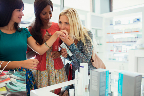Women smelling perfume in drugstoreの写真素材 [FYI02187371]