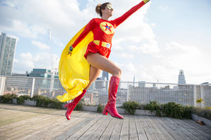 Superhero jumping on city rooftopの写真素材 [FYI02187382]