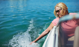 Older woman trailing hand in water from boatの写真素材 [FYI02187393]