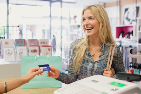 Woman paying with credit card in clothing storeの写真素材 [FYI02187413]