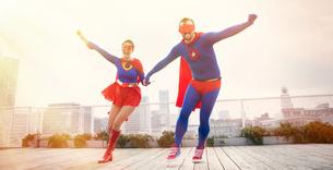 Superheroes holding hands running on city rooftopの写真素材 [FYI02187416]