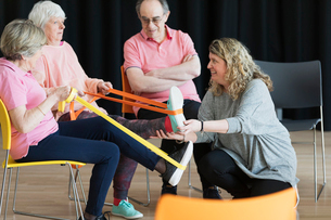 Instructor helping active seniors stretching legs, exercising with strapsの写真素材 [FYI02187425]