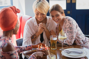 Young women friends celebrating birthday with cake in restaurantの写真素材 [FYI02187448]