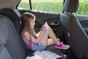 Girl doing homework in back seat of carの写真素材 [FYI02187457]