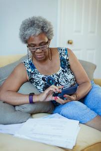 Senior woman with calculator reviewing billsの写真素材 [FYI02187465]