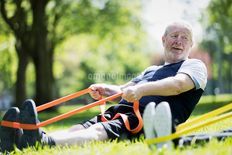 Active senior man exercising in park, stretching with resistance bandの写真素材 [FYI02187466]