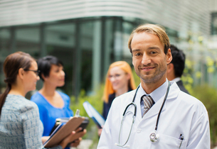 Portrait of smiling doctor wearing lab coat standing in front of hospital, women with clipboards inの写真素材 [FYI02187483]