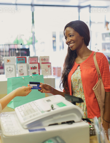 Woman paying with credit card in drugstoreの写真素材 [FYI02187544]