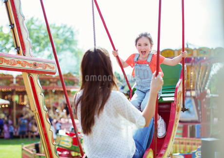 Mother and daughter playing on swing in amusement parkの写真素材 [FYI02187548]