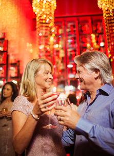 Mature couple standing face to face and holding drinks in nightclubの写真素材 [FYI02187555]