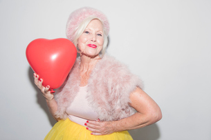 Portrait confident senior woman in fur holding heart-shape balloonの写真素材 [FYI02187591]