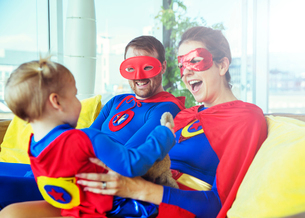 Superhero parents playing with daughter on living room sofaの写真素材 [FYI02187596]