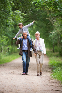 Couple walking with grandson on rural roadの写真素材 [FYI02187609]