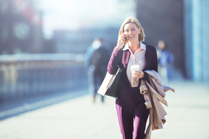 Businesswoman talking on cell phone on city sidewalkの写真素材 [FYI02187627]