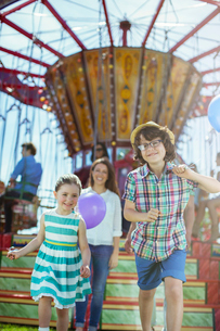 Children running in front of carousel, mother following themの写真素材 [FYI02187641]