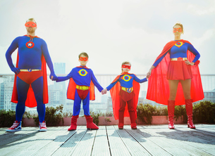 Superhero family holding hands on city rooftopの写真素材 [FYI02187646]
