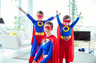 Superhero children and mother smiling in living roomの写真素材 [FYI02187648]
