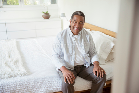 Portrait of smiling senior man sitting on bedの写真素材 [FYI02187741]