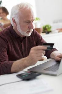 Focused senior man with credit card paying bills at laptopの写真素材 [FYI02187742]